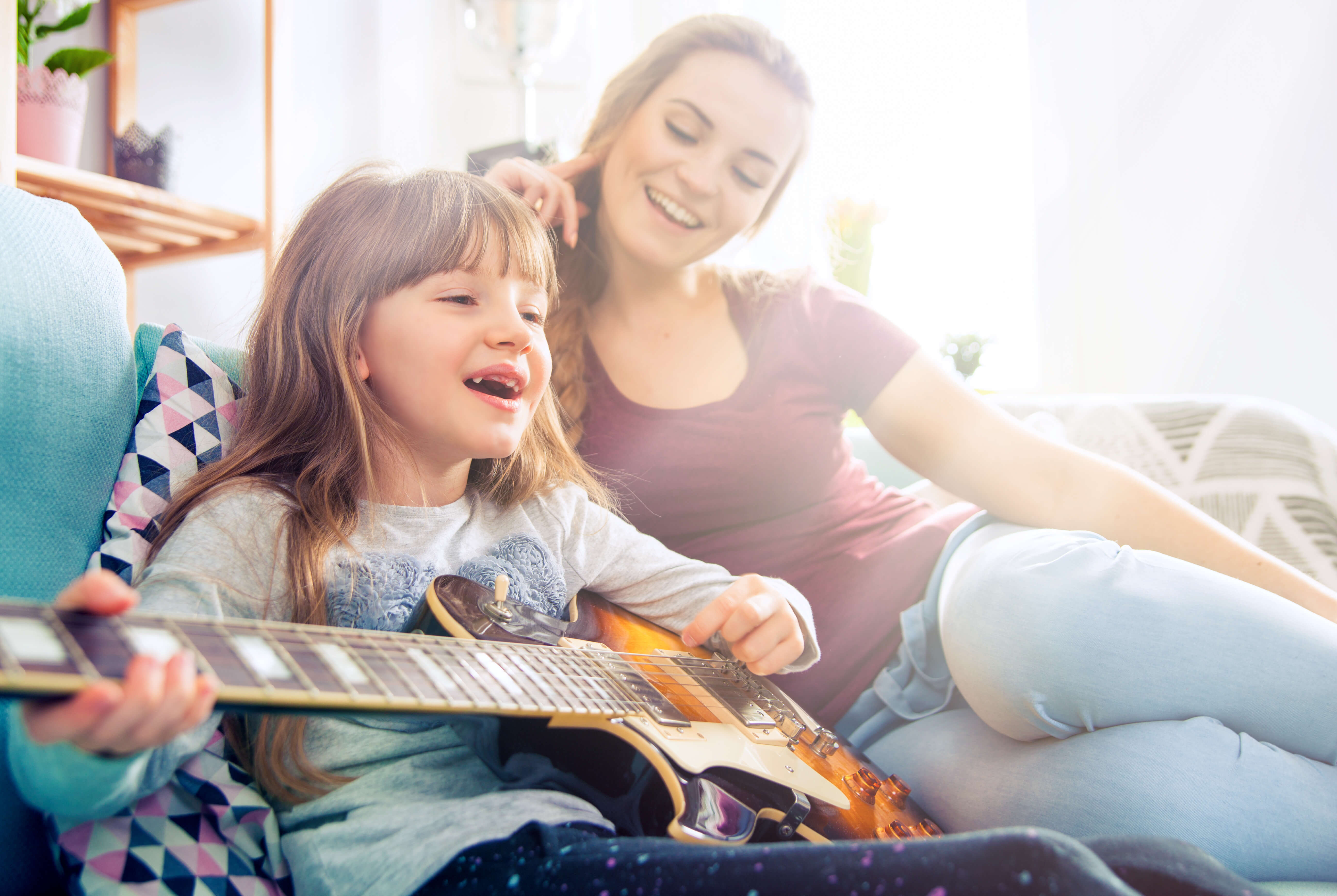 Mother and daughter at home playing guitar and singing
